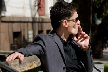 Smoking young man in sunglasses