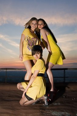 Three sexy young women in yellow dresses posing