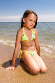 Little girl sitting at the beach