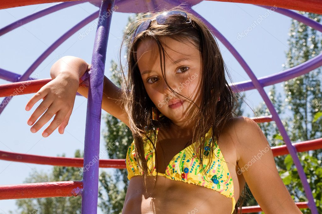 Young girl at playground in summer day