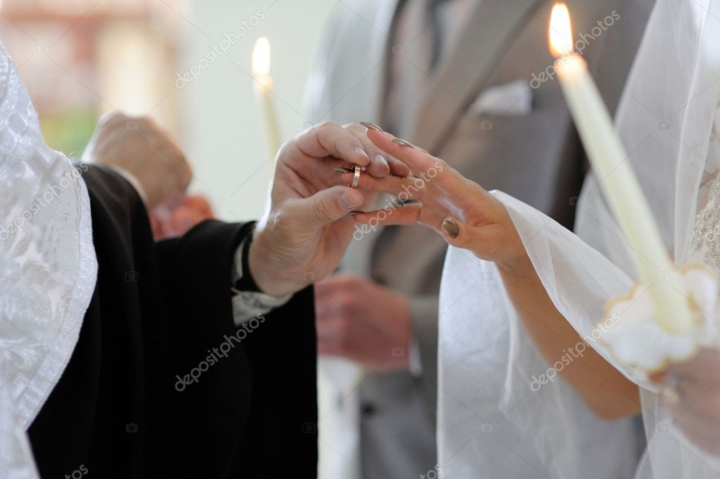 Priest putting the ring on brides finger Stock Photo maximkabb