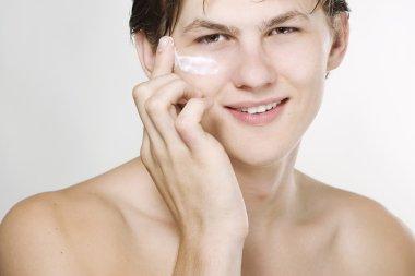 Handsome man applying cream