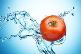 Tomato in spray of water.