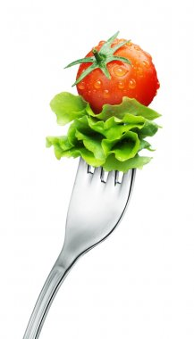 Fresh red tomato and salad on a fork