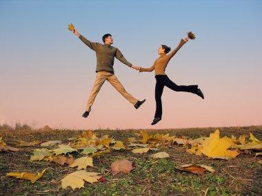 Jump couple. autumn leaves. sunset sky