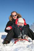 zimní otec s dítětem na saně