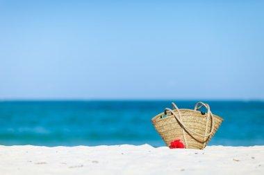Straw beach bag on exotic white sand beach