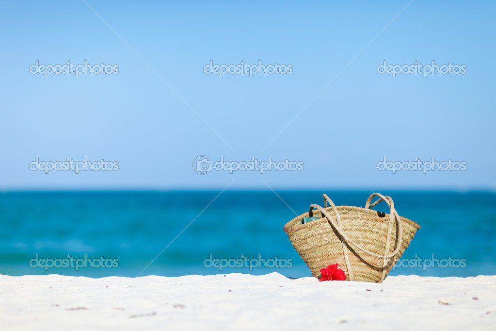 Straw beach bag on exotic white sand beach