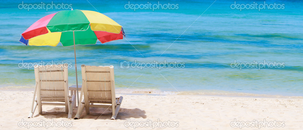 Panorama of tropical beach with chairs and umbrella