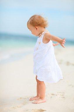 Toddler girl in white dress at beach