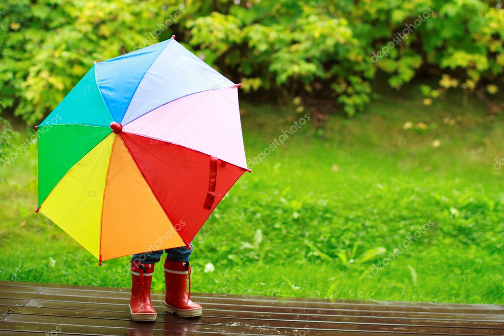 Little girl hiding behind umbrella