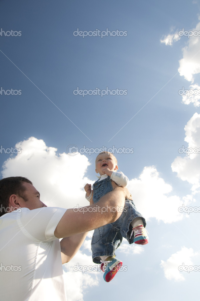 Father throws baby son in her arms on a background of blue sky, paternal care