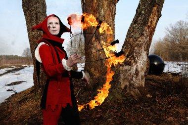 Artistic woman in a suit of fire-clown holds a fiery fan posing