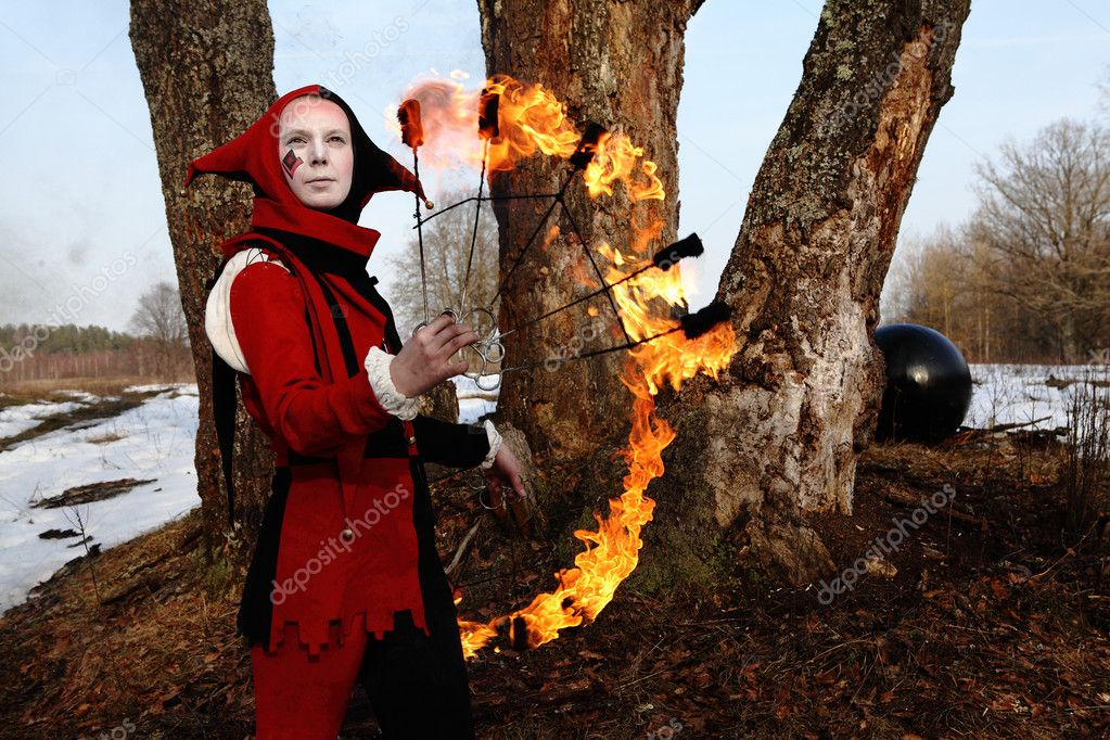 Artistic woman in a suit of fire-clown holds a fiery fan posing