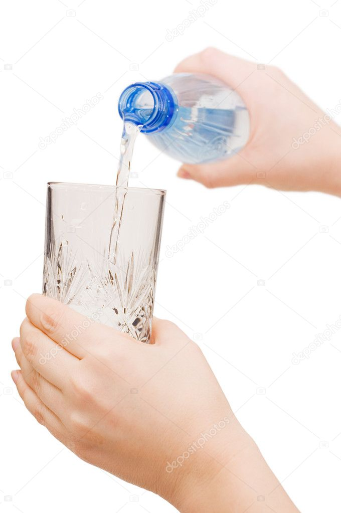 The girl pours water in a glass