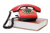 Fotografia telefono rosso sul libro isolato