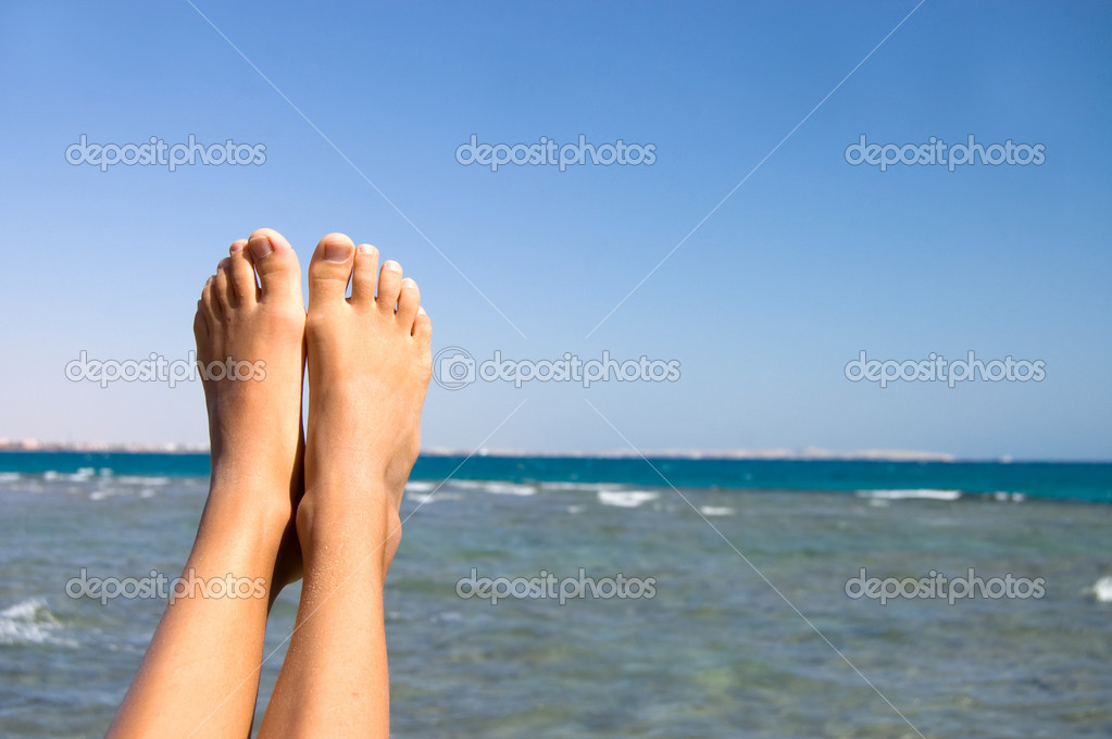 Female feet against the sea