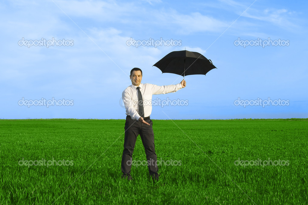 Happy businessman standing with umbrella