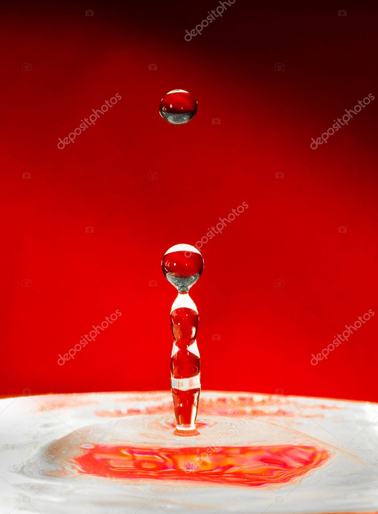 Falling drops of water over red