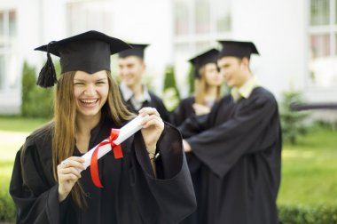 A graduate holding a diploma and smiling