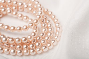 Pearl necklace over white silk
