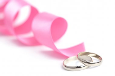 Gold wedding rings and pink ribbon isolated