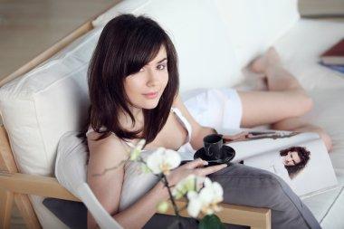 Young beautiful girl reads magazine