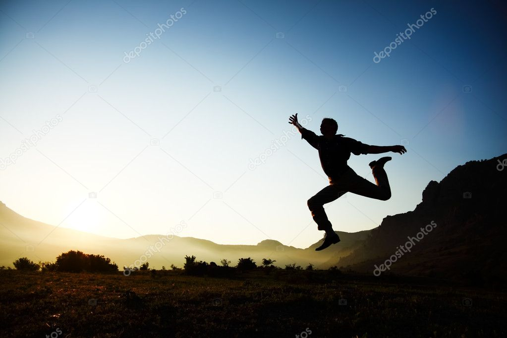 Silhouette of a young male jumping over sunset background with copyspace