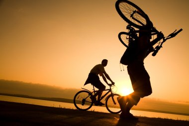 Man carries a bicycle at sunset