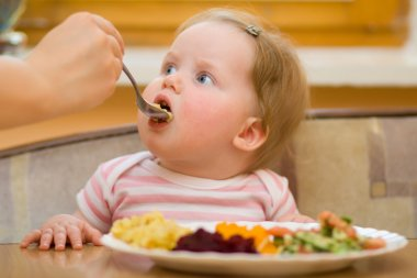 The child eats a vegetable salad