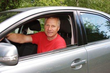An elderly man is in a car