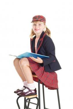 Teen girl in school uniform reading a book