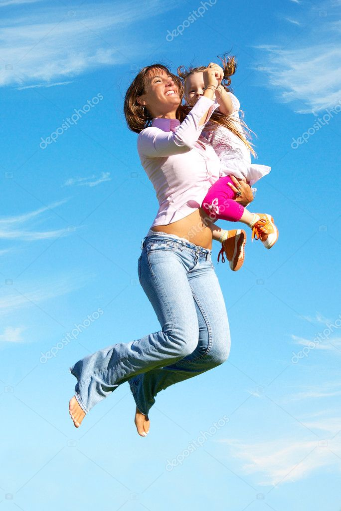 Mother and daughter jumping