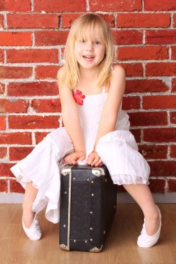 Beautiful little girl sitting on a suitcase