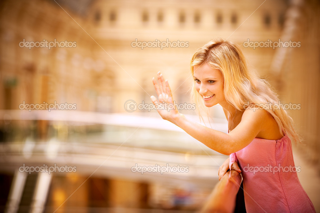 Beautiful young woman waves hand, leaning against handrail. In magnificent hall.