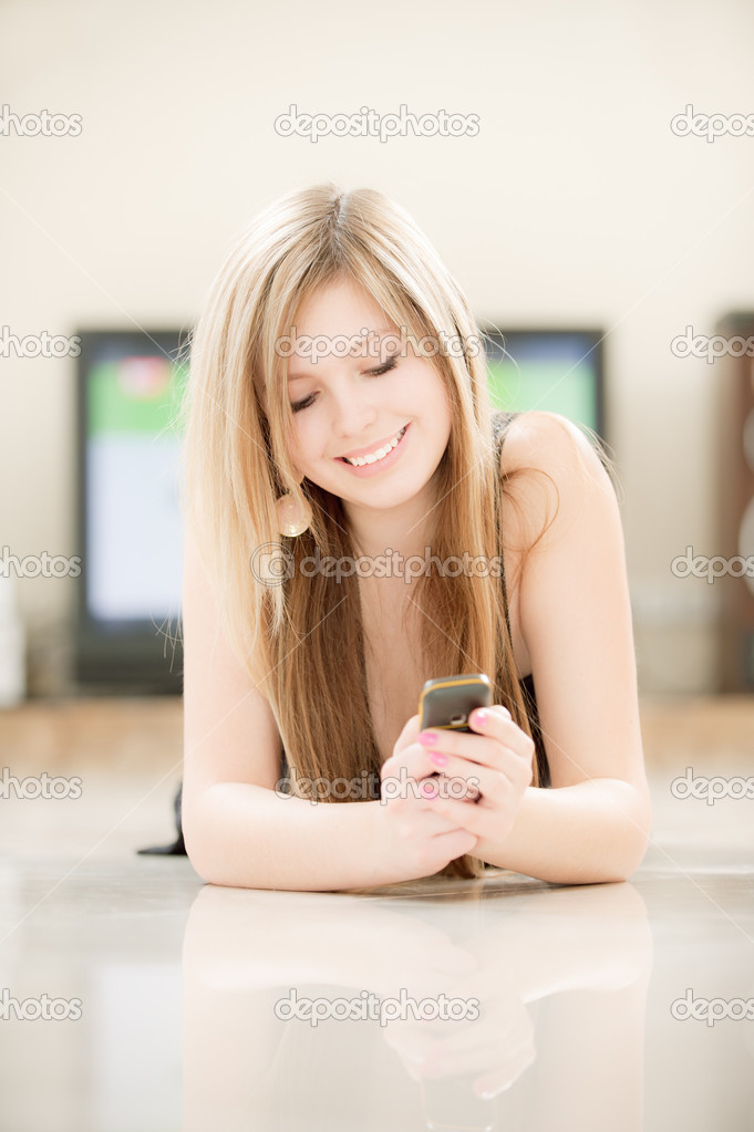 Smiling girl reads sms.