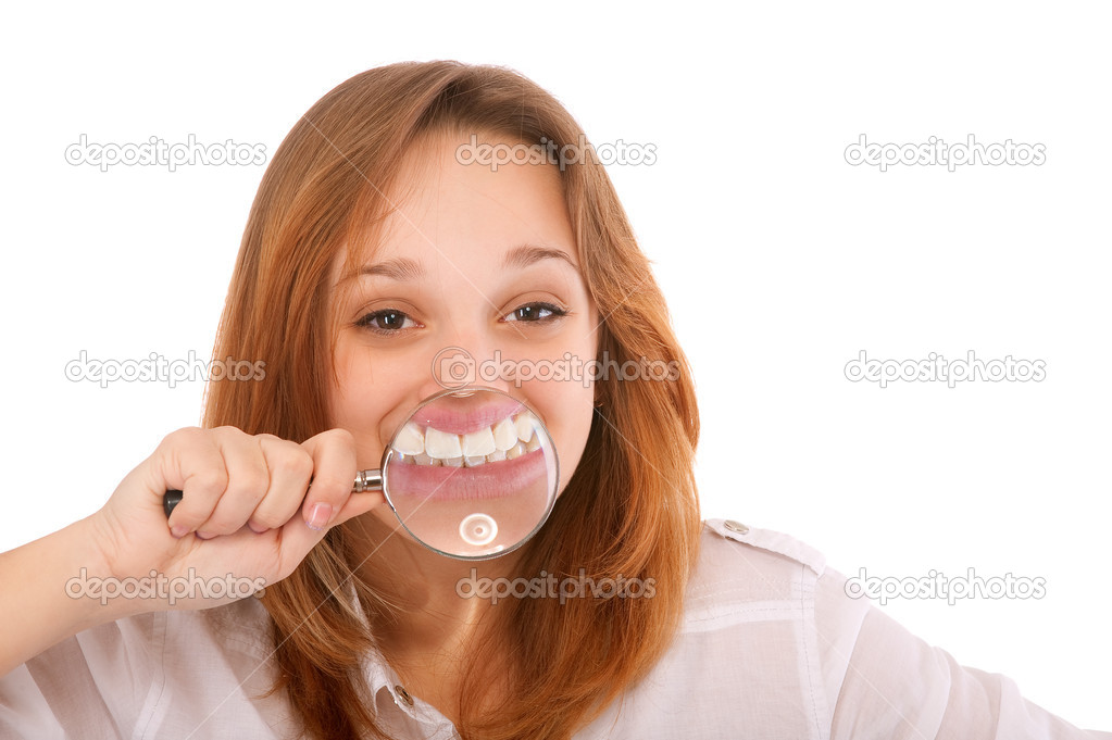 Teeth of young woman through magnifier