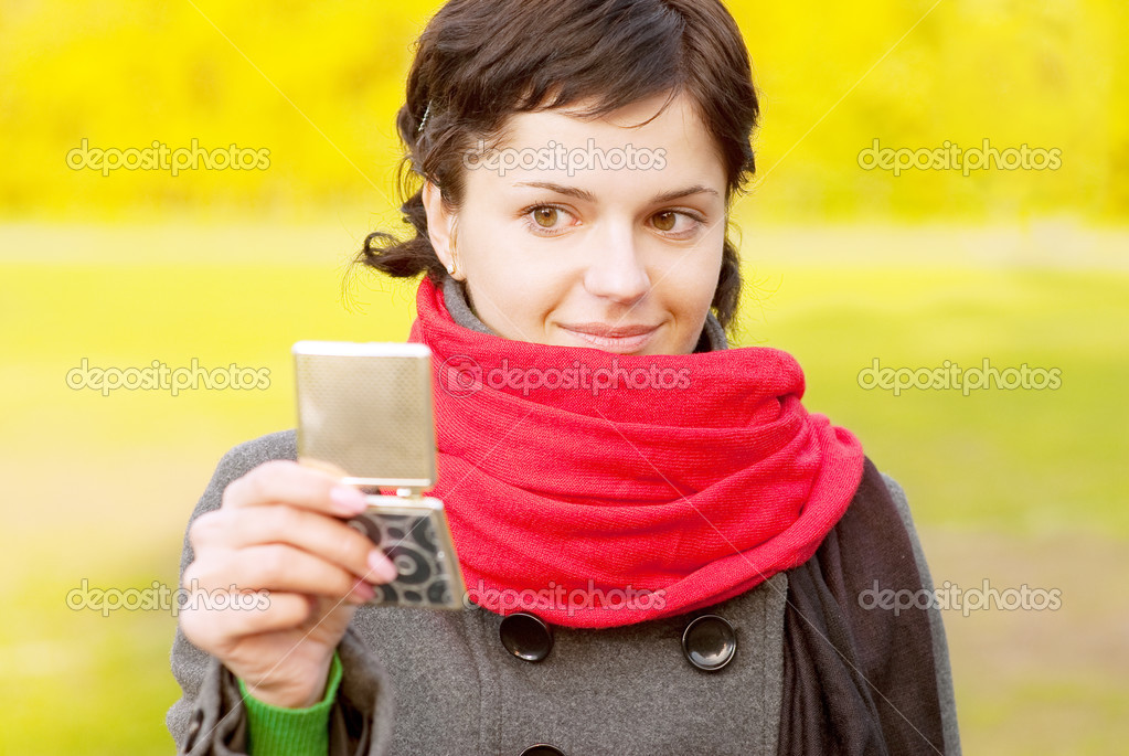 Girl with red scarf looks in mirror