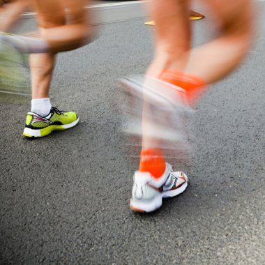 Man running in city marathon - motion blur