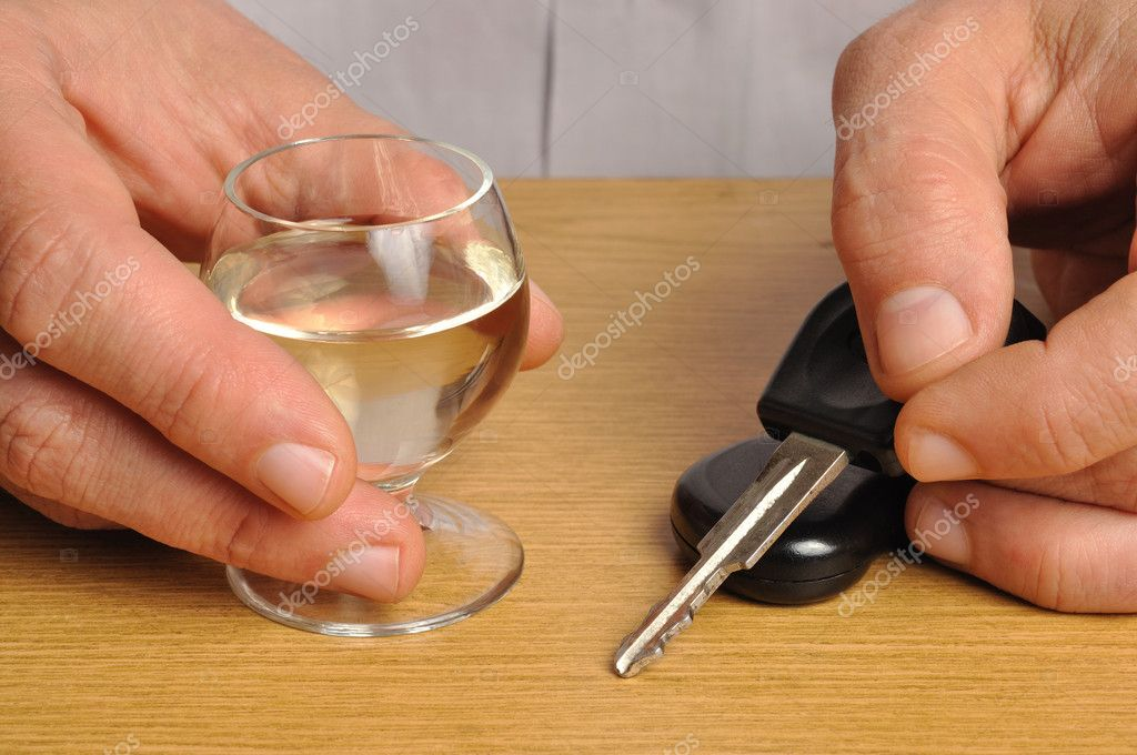Someone with alcohol and car keys on a table