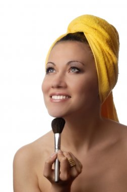 Photo of smiling model in yellow towel with cosmetic brush stock vector