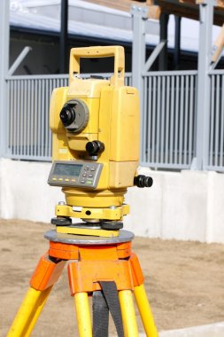 Yellow theodolite on a construction site