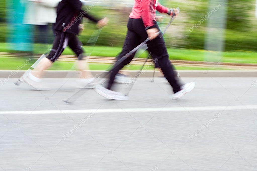 Women on nordic walking race, blurred