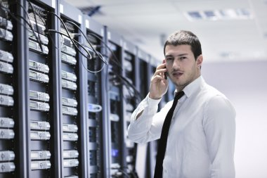 It engeneer talking by phone at network room