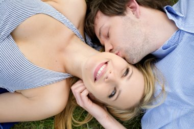 Young happy couple laying on grass