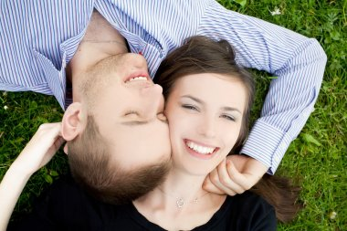 Smiling young couple is cuddle on a gree