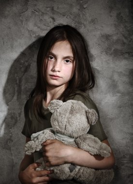 Sad little girl with toy