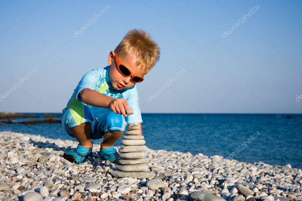 Boy building stone stack