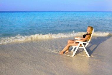Woman tans in beach chair in ocean