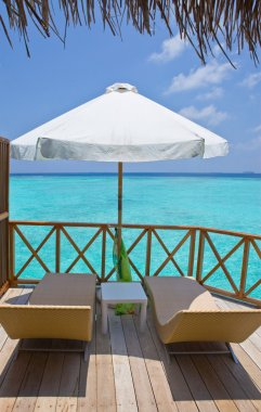 Parasol and chaise lounges on a terrace of water villa, Maldives.
